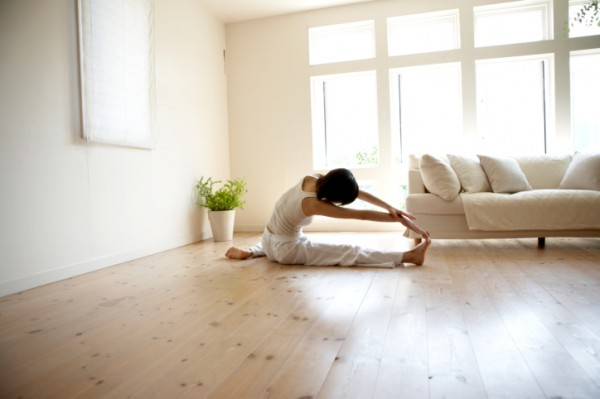 Yamanashi Prefecture, Japan. low-angle view of woman in yoga pose on wooden living room floor with large windows letting in lots of natural sunlight